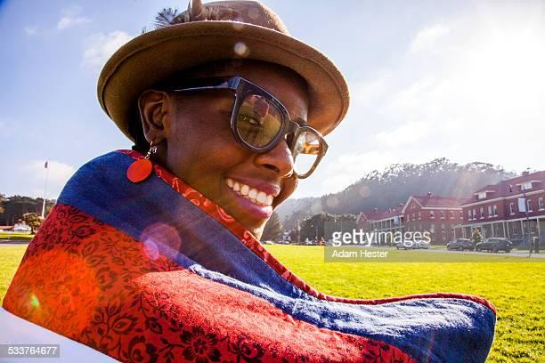 Black woman wrapped in blanket in urban park
