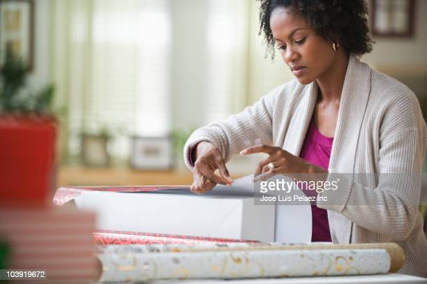 Black woman wrapping gift