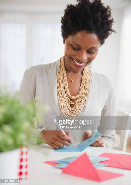 Black woman writing on birthday card