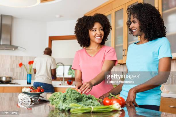 Black women chopping vegetables in kitchen