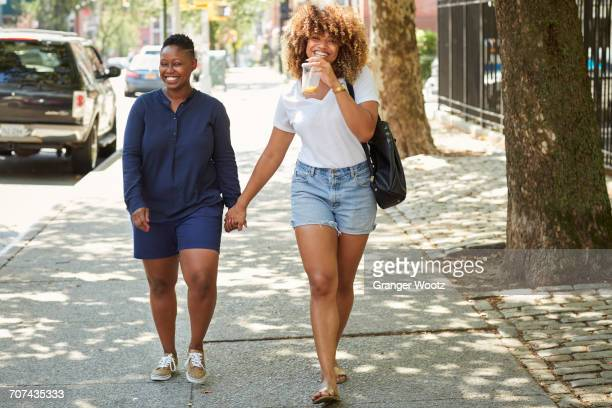 Black women holding hands on city sidewalk