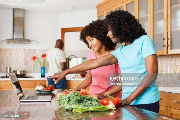 Black women using digital tablet and chopping vegetables in kitchen