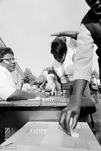 Black women vote for the first time in an Alabama town after the enactment of the Voting Rights Act.