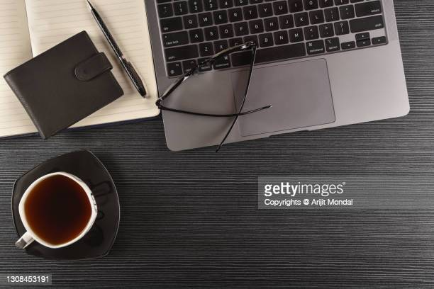 black wooden background of work desk table with computer keyboard, black tea, eyeglasses, wallet, pen copy space - multimedia stock pictures, royalty-free photos & images