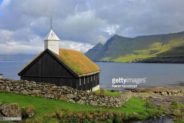 a black wooden church with a grassy roof on the coast of a bay - rainer grosskopf stock-fotos und bilder