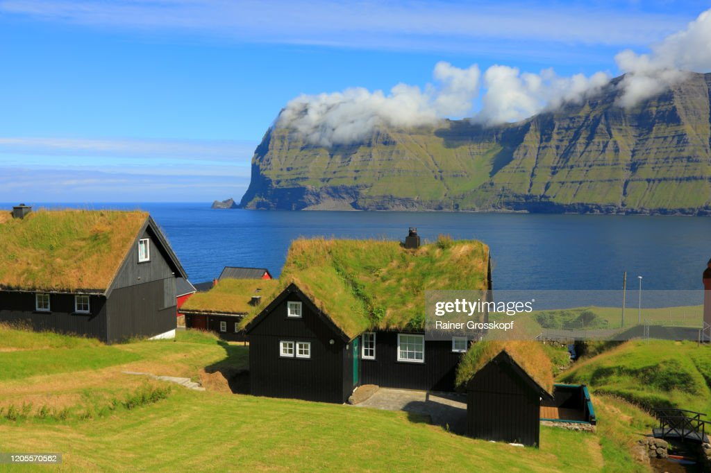 Black wooden houses with grassy roofs in a small northern village on the shore of the sea : Stock-Foto