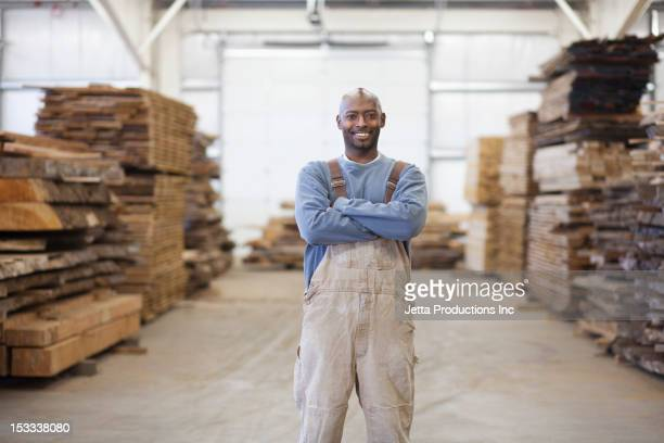 black worker in lumber warehouse - bib overalls stock pictures, royalty-free photos & images