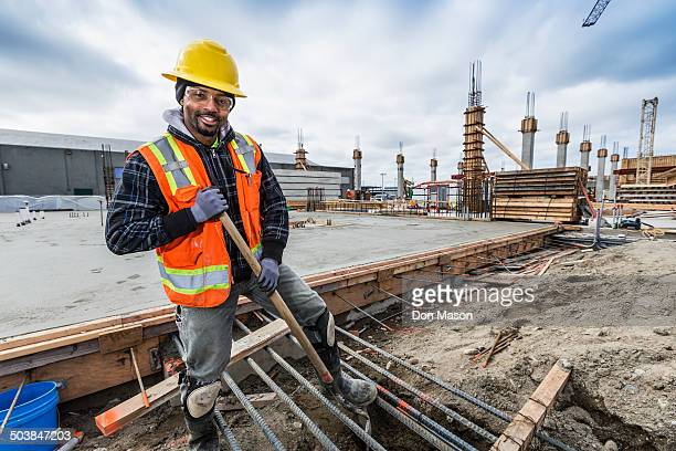 black worker smiling at construction site - black boot stock pictures, royalty-free photos & images