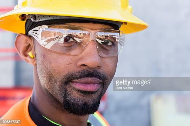 black worker smiling on construction site - schutzbrille stock-fotos und bilder