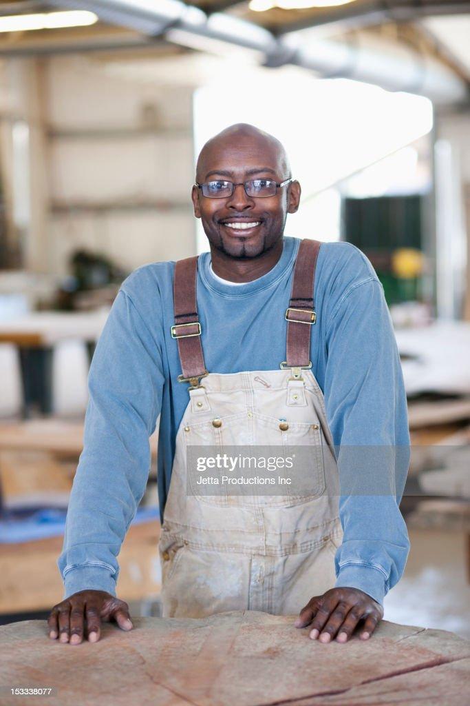 Black worker standing in factory : Stock Photo