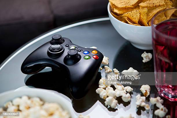 A black XBox 360 wireless controller photographed on a glass table surrounded by bowls of snacks taken on July 9 2013