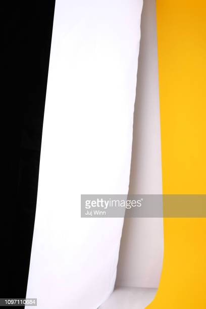 Black, yellow and white papers on a white backdrop with shadow.