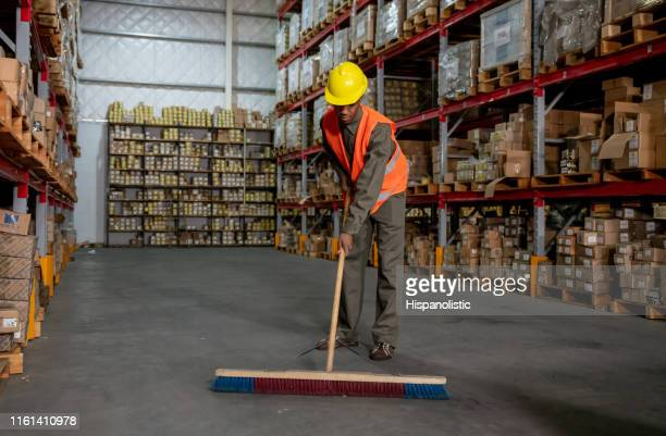 black young man working at a distriution warehouse sweeping the floor - sweeping stock pictures, royalty-free photos & images