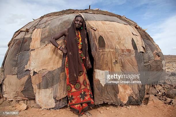 CONTENT] A black young woman belonging to the tribe of Gabbra dressed in a colorful robe smiling at the entrance of her home in the Chalbi Desert...
