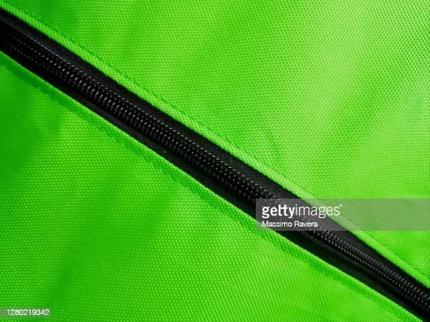 black zip on green fabric. - ファスナー ストックフォトと画像