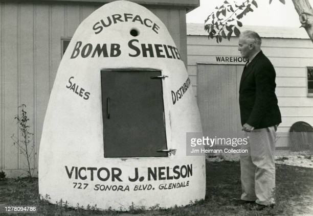 Black-and-white photo shows a man standing next to a surface bomb shelter that is advertising Victor J. Nelson's sales and distribution business,...