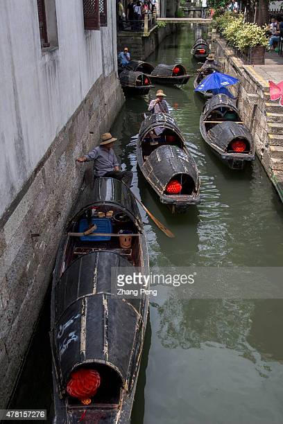 Blackawning boats stop at a dock The boat also known as a Chinese gondola covered with an awning that is woven with thin bamboo strips and painted...