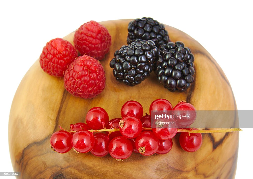 Blackberries, red currants and raspberries on a olive wood surface : Stock Photo