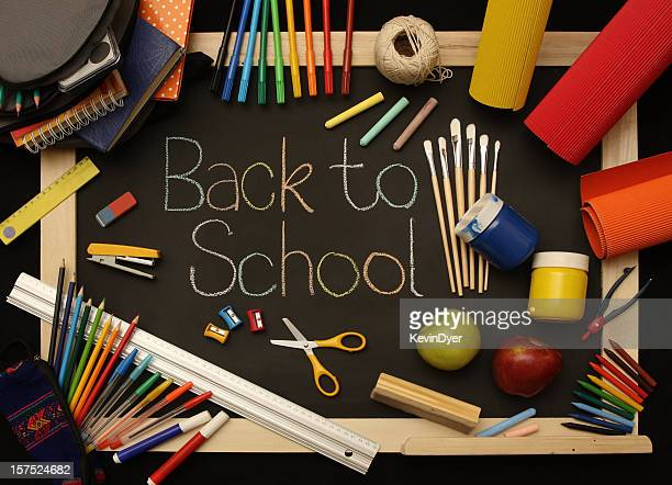 a blackboard covered in school supplies with back to school - pencil case stock photos and pictures