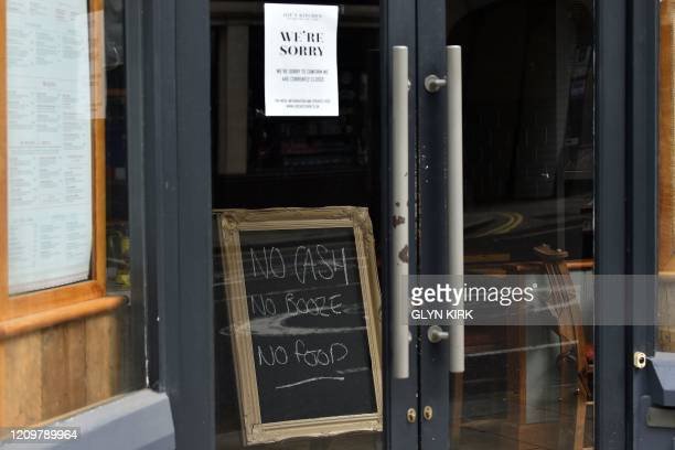 A blackboard inside the doors of a restaurant displays a message saying No cash No booze No food as tourists stay away on the bank holiday Monday in...