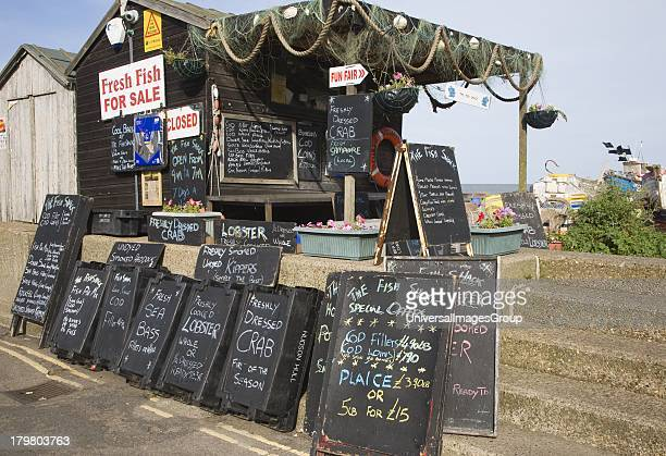 Blackboard offers for fresh fish on sale outside beach shed Aldeburgh Suffolk England