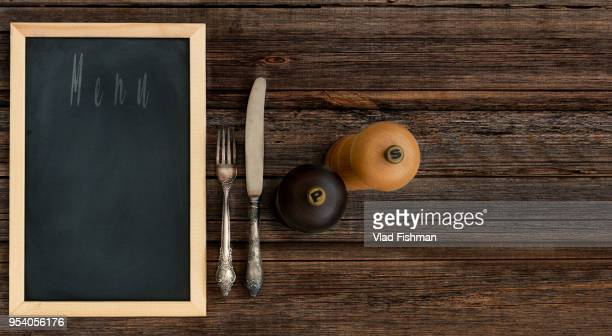 blackboard restaurant menu with vintage silverware or cutlery on a wood rustic table background. - menu stock pictures, royalty-free photos & images