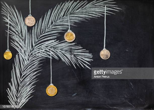 Blackboard with a chalk drawing of spruce branch and coins as decoration. Christmas background