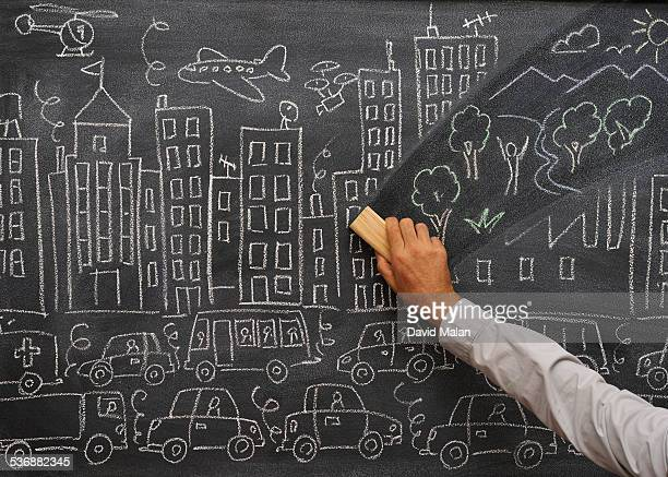 Blackboard with a city, wiped to reveal nature