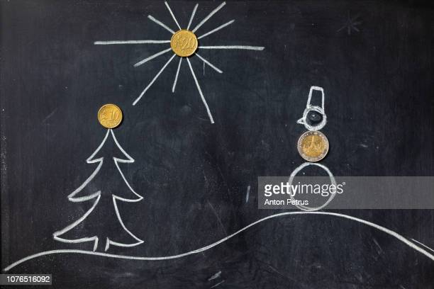 Blackboard with a drawing of a winter landscape and coins as decoration. Christmas background