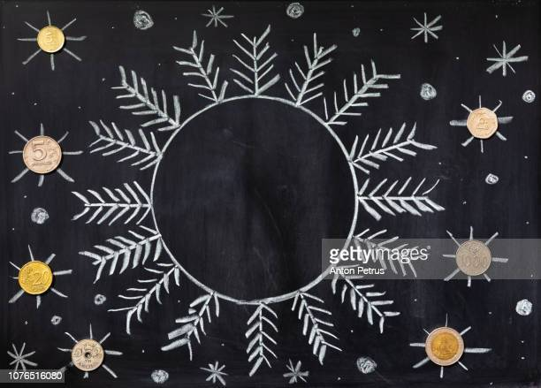 Blackboard with a drawing of snowflakes and coins. Christmas background