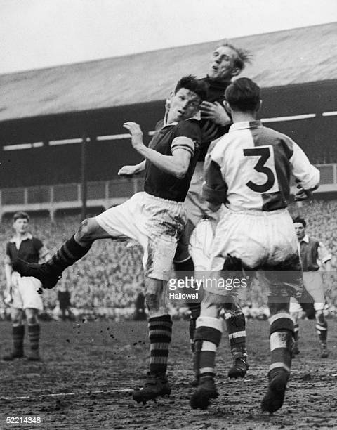 Blackburn goalkeeper Reg Elvy and defender Bill Eckersley number 3 leap to defend a shot from a Burnley striker during a sixth round F A Cup tie...