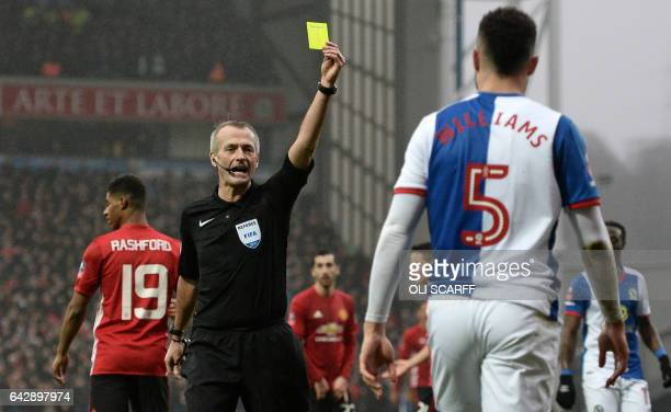 Blackburn Rovers' Irish defender Derrick Williams receives a yellow card during the English FA Cup fifth round football match between Blackburn...