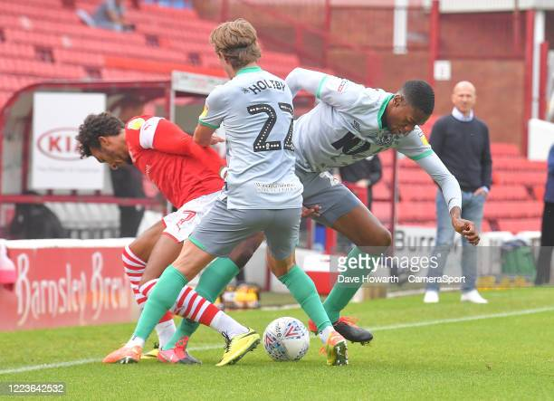 Blackburn Rovers' Lewis Holtby and Tosin Adarabioyo battle with Barnsley's Jacob Brown during the Sky Bet Championship match between Barnsley and...