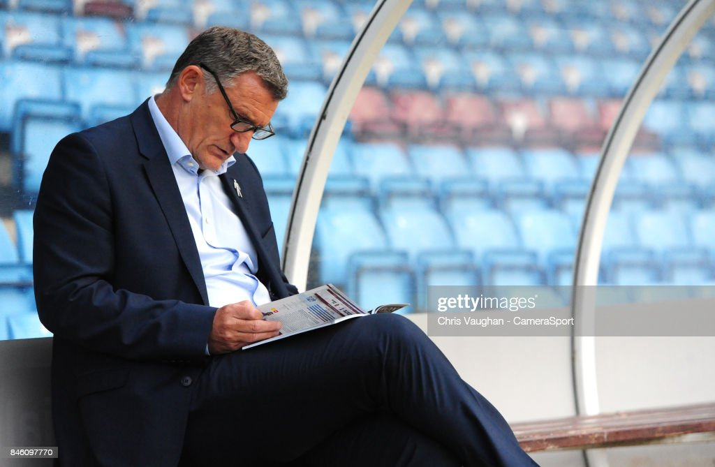 Blackburn Rovers manager Tony Mowbray reads a copy of the match day program, whilst sat in the dug-out, after arriving at the ground prior to the Sky Bet League One match between Scunthorpe United and Blackburn Rovers at Glanford Park on September 12, 2017 in Scunthorpe, England.