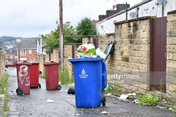 """Blackburn with Darwen Borough Council"""" logo is pictured on an overflowing wheelie bin behind a row of terraced houses in a residential street in..."""