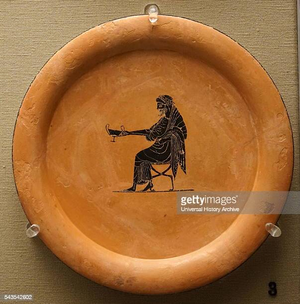Blackfigured plate depicts Dionysos god of wine holding out a drinking cup whilst seated made in Athens Dated 6th Century BC
