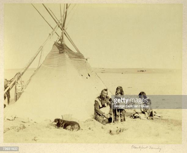 A Blackfoot Indian family father mother two children and a pet dog sit outside their teepee tent house on the Great Plains Blackfeet Indian...