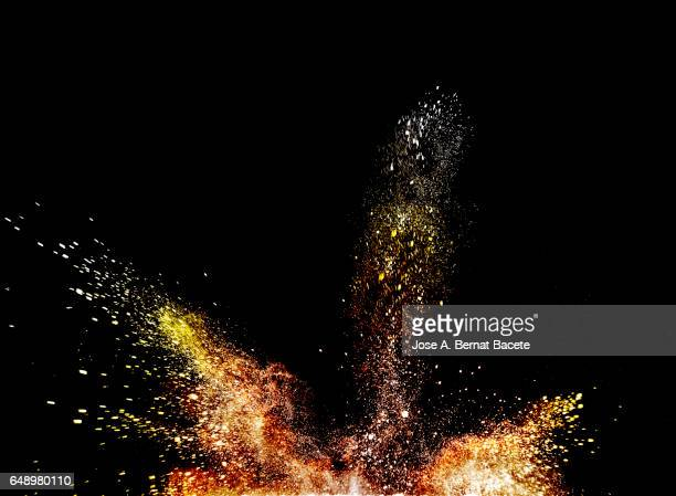 Blackground of particles of red and orange powder in ascending movement floating in the air produced by an impact