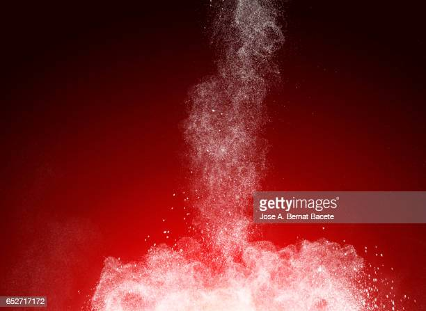 Blackground of particles of white powder in ascending movement floating in the air produced by an impact