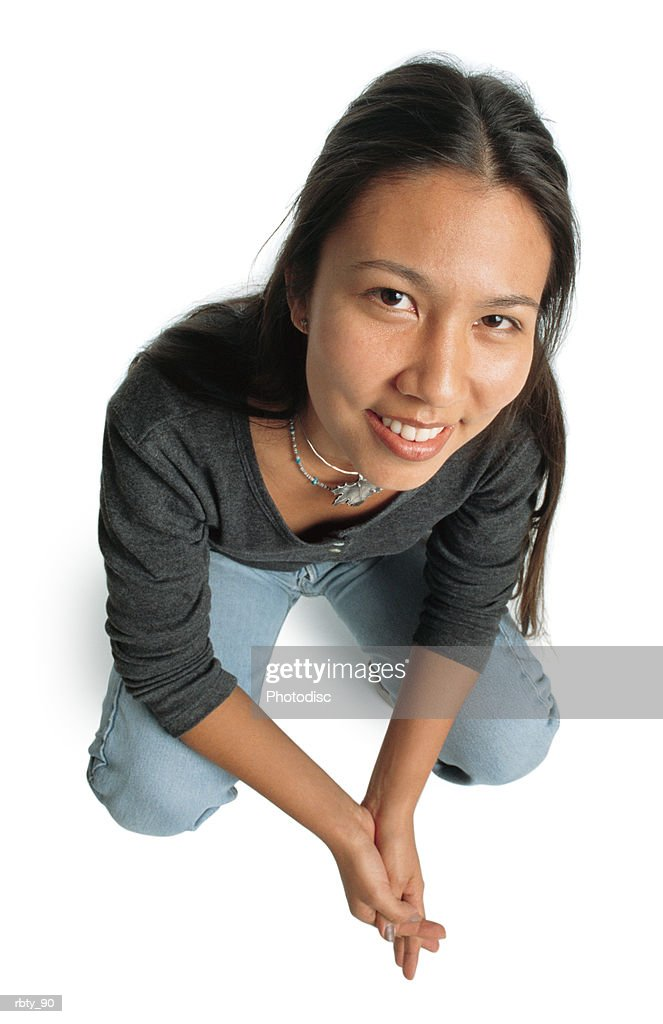 black-haired asian teenage girl wearing blue denim jeans and a black long-sleeve shirt crosses her hands as she crouches and looks up toward the camera as she smiles : Foto de stock