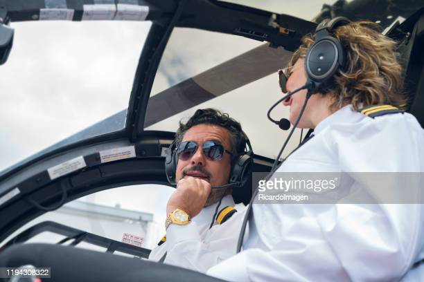 black-haired man with a beard of approximately 40 years dressed in his pilot uniform accompanied by a blue helicopter cockpit, his co-pilot latin woman with short blond hair and pilot uniform is soon to take off - 55 59 years stock pictures, royalty-free photos & images
