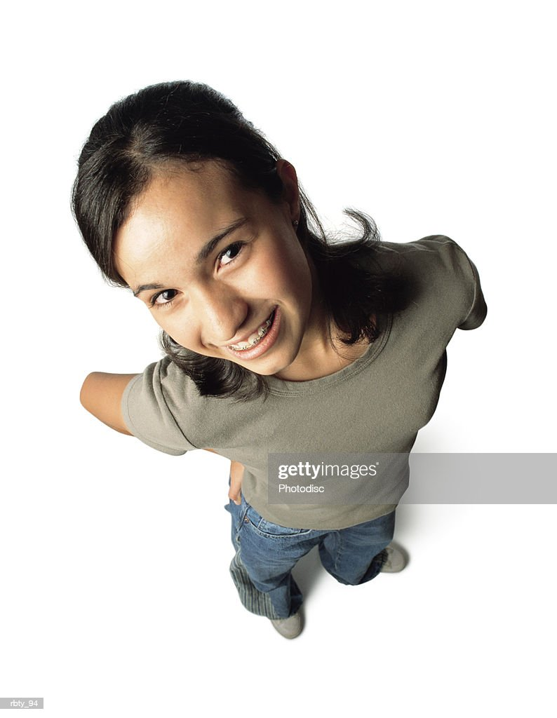 black-haired teenage girl wearing blue denim jeans with white shoes and a green shirt puts her hands on her hips as she smiles and looks up toward the camera : Foto de stock