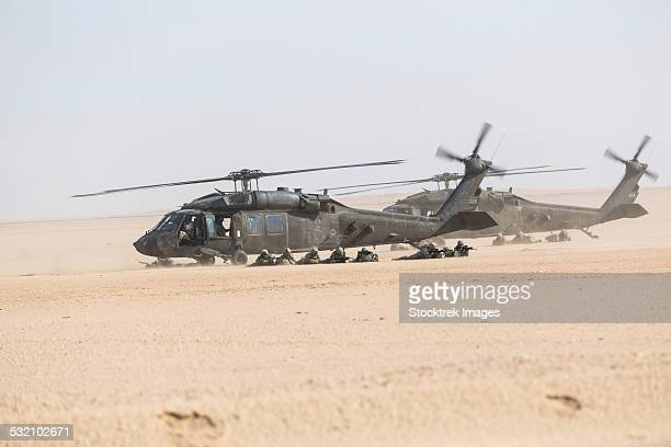 UH-60 Blackhawk helicopters air drop soldiers in Kuwait.