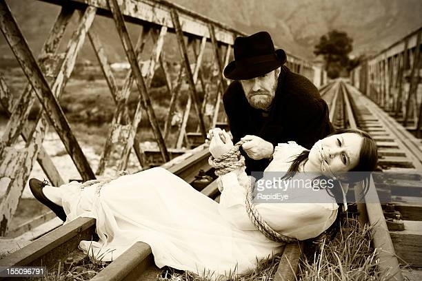 black-hearted villain, kidnapped maiden, victorian melodrama at its best - bound woman stock photos and pictures