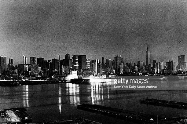 The Manhattan skyline reflects isolated pockets of emergency generating light late Wednesday night after blackout Lights are provided by generators...
