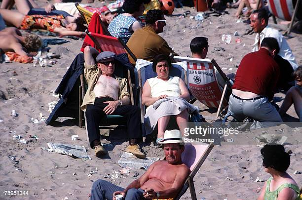 Blackpool England A couple relaxing on a deck chair as they try to sun bathe on a beach in Blackpool England
