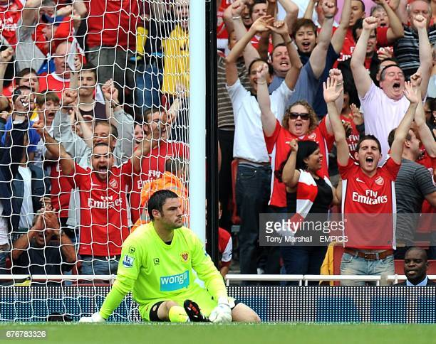 Blackpool goalkeeper Matthew Gilks sits dejected in front of celebrating Arsenal fans after Theo Walcott scored the opening goal