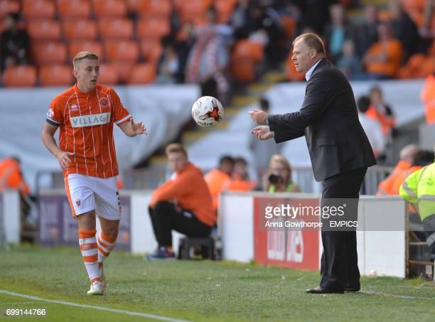 Blackpool manager Neil McDonald throws the ball to David Ferguson