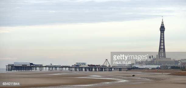 Blackpool Tower is seen rising above a pier and a beach in Blackpool north west England on February 6 2017 Blackpool is a seaside resort in the...