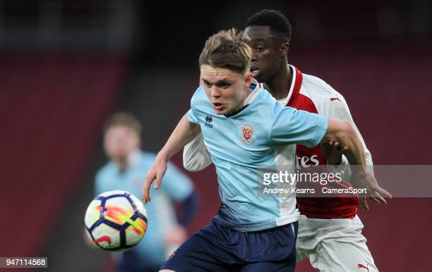 Blackpool U18's Finn SinclairSmith holds off Arsenal U18's James Olayinka during the FA Youth Cup Semi Final Second Leg match between Arsenal U18 and...